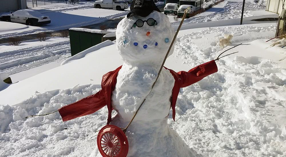Our front-yard snowman with his whiskey hat and stick-guitar.